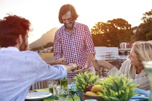 Man serves friends skewer kababs at outdoor rooftop barbeque dinner party